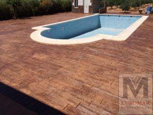 construyendo el piso de hormigón impreso madera al rededor de la piscina